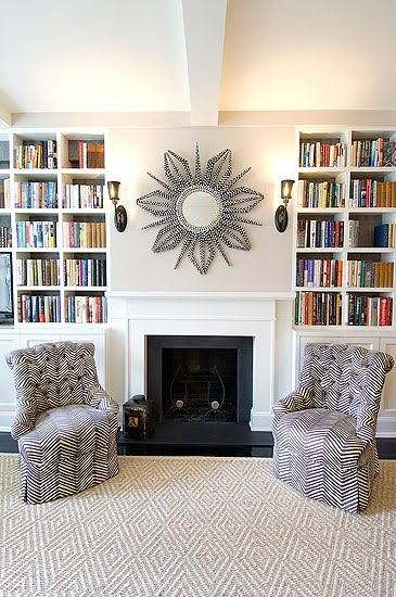 Living room with herringbone printed armchairs, a fireplace, graphic print area rug and built in bookshelves