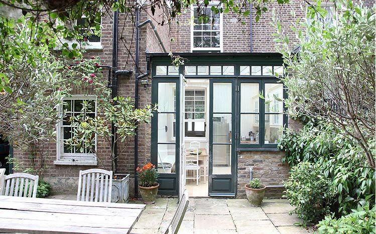 Brick exterior of a London home and the outside of the glass kitchen