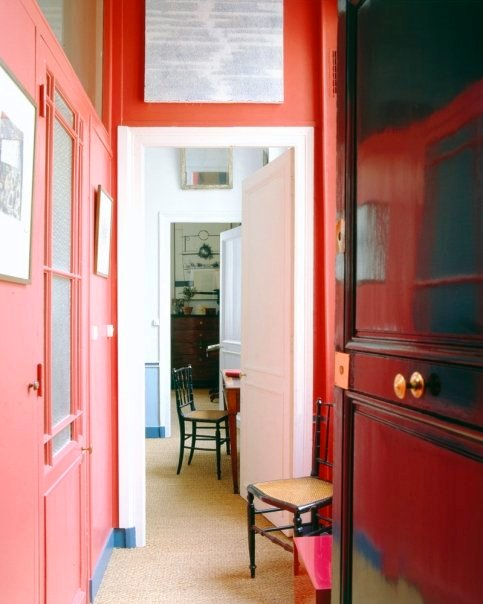 Coral hallway with a white door in a Paris apartment