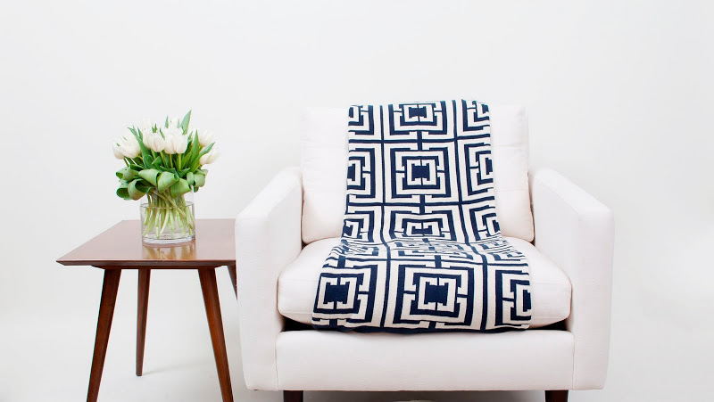 COCOCOZY Logo cotton knit reversible throw in navy on a white chair next to some beautiful Belgian tulips