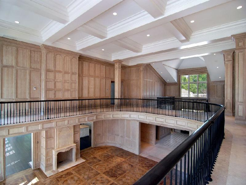 Second floor with light wood paneling, black railing and a coffered ceiling