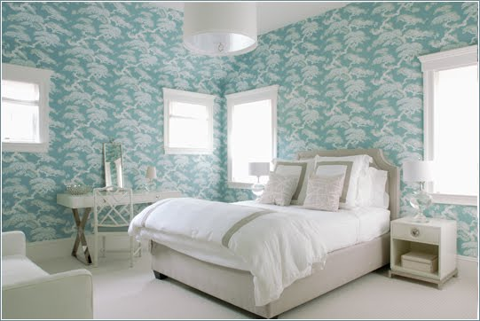 Bedroom with floor to ceiling blue toile wallpaper, windows, a white nightstand, upholstered headboard and an oval pendant light