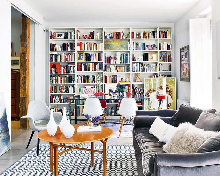 Alternative view a living room in an apartment with built in bookshelves, a grey sofa, grey armchair, wood table, a blue and white graphic print rug and a glass table surrounded by Eames chairs