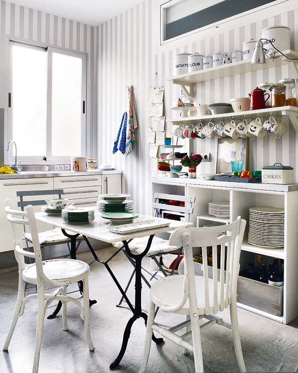 Alternative view of the apartment kitchen with grey and white striped walls, white drawers with long drawer pulls, stainless counter top, open shelving, an table with iron legs and a marble top and mismatched chairs
