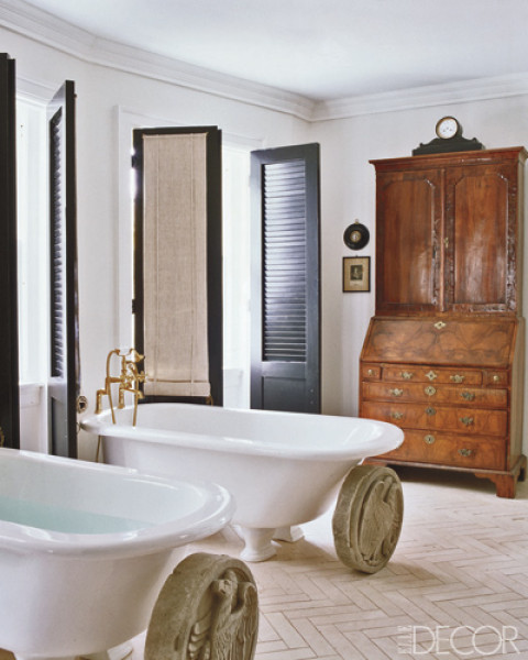 Bathroom with herringbone tile floor, two stand alone tubs, black doors and large roman coines