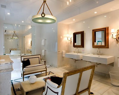 Bathroom with dueling settees, two wall mounted sinks, marble tile floor, a large mirror and an oval pendant light