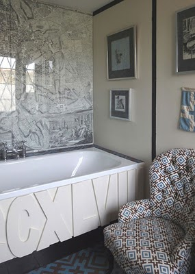 Bathroom with a large map on the wall, a step in tub with CCXLVIII written on the side, a blue and brown rug and a tufted armchair with a graphic brown, blue and white pattern