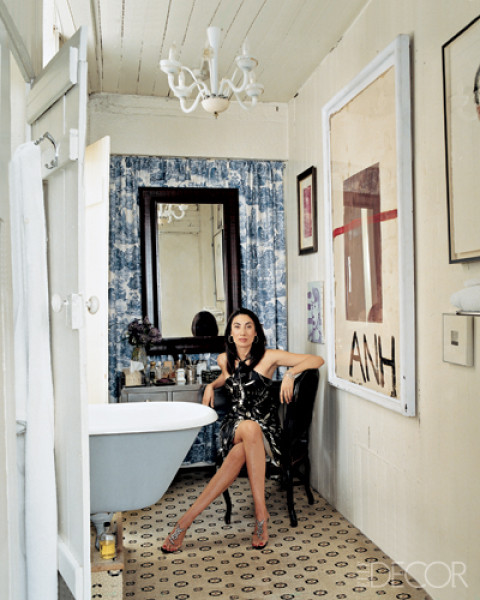 Ahn Duong in her bathroom with a stand alone tub, round tile floor, white chandelier, instead of a back wall, she's hung a blue and white curtain behind a black mirror