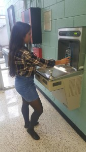 Sophomore Vanessa Sanoja illustrates how to use the water bottle filling station