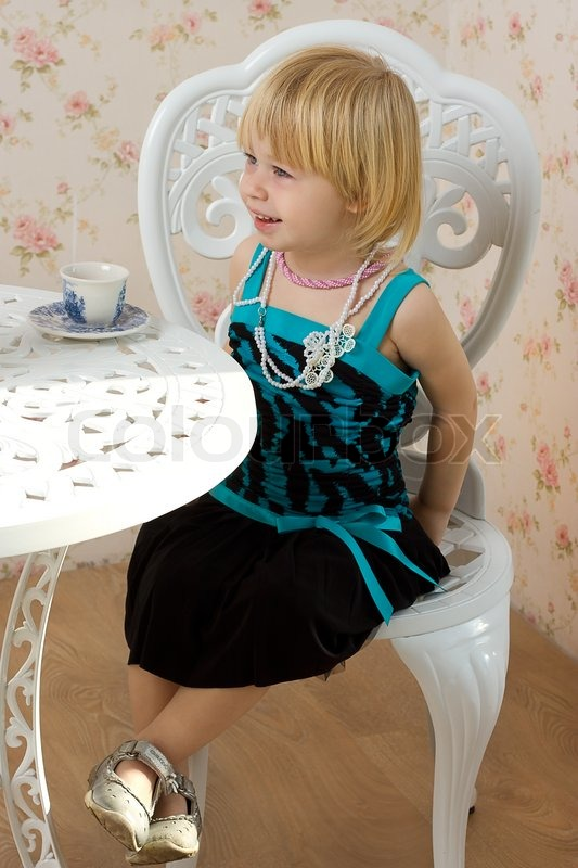Sitting Sessel The Little Girl In A Dress Sitting On A Chair | Stock
