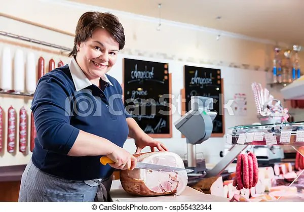 Experienced butcher shop assistant cutting ham to sell it - shop assistan