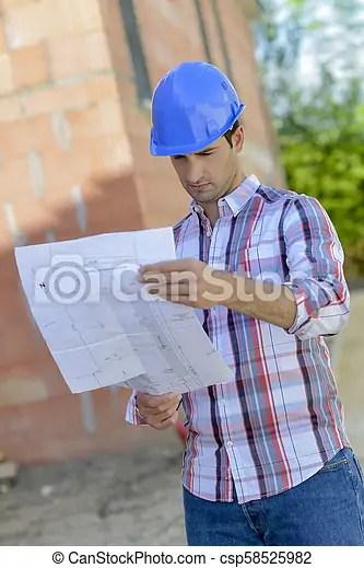 Architect reading blueprints on site