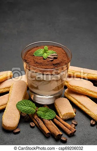 Classic tiramisu dessert in a glass and savoiardi cookies on dark concrete background or table.