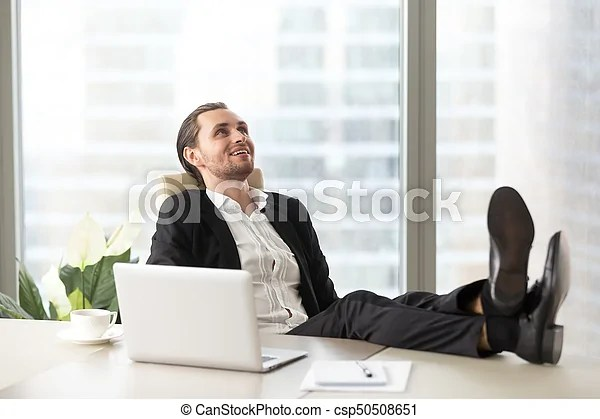 Happy smiling businessman relaxing at workplace in modern office