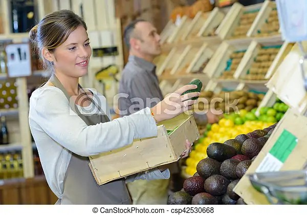 Shop assistant stacking shelf with avocados - shop assistan