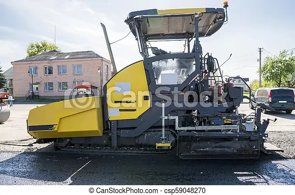 Worker operating asphalt paver machine during road construction and - asphalting machine