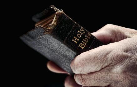 man-hands-holding-old-bible-olivier-le-queinec