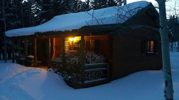 Trout Run Hunting cabin with firewood at dusk