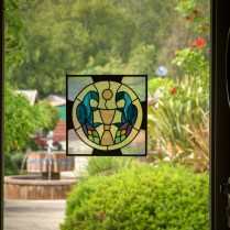 Handmade stained glass version of our Camaldolese stemma (coat of arms) looking into the cloister garden.