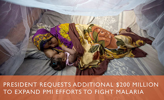 A mother and her child lay on a bed under treated mosquito nets.