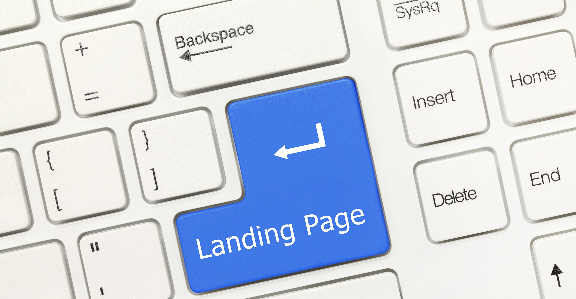Close-up view on white conceptual keyboard - Landing Page (blue key)