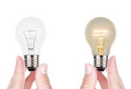 fingers holding 2 light bulbs-one lit