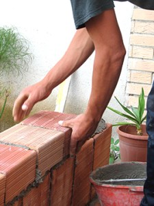 Man's arms laying bricks around a patio