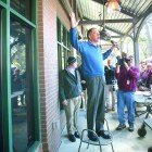 Ohio Gov. John Kasich, a Republican presidential hopeful, stands on a chair to greet an overflow crowd outside a campaign stop at Finn's Brick Oven in Mount Pleasant, S.C., Feb. 10, 2016. The Ohio governor savored his come-from-behind finish on Tuesday, but the road ahead for his presidential campaign remains arduous and uphill.