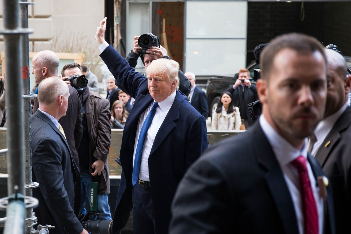 Republican presidential hopeful Donald Trump waves after giving reporters a tour of the site for the Trump International Hotel Monday.
