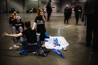 A family of Trump supporters sits on the group before the candidate's rally Saturday.