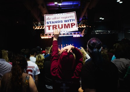 Supporters hoist signs at a Donald Trump rally Saturday.