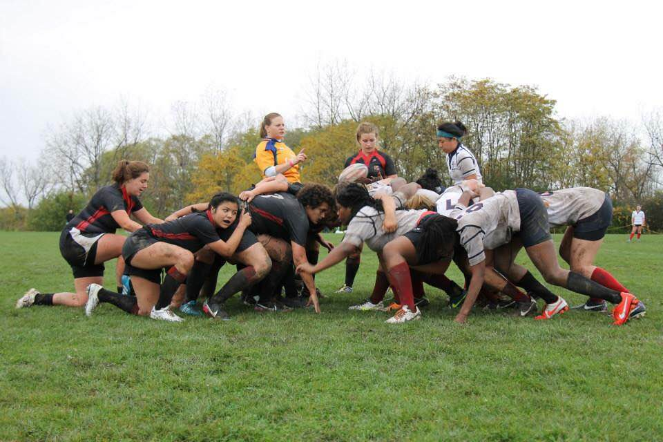 The Cornell women's rugby team in a scrum, getting ready to play.