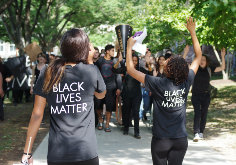 "Marchers shout ""hands up, don't shoot"" at a Black Students United rally on Friday."