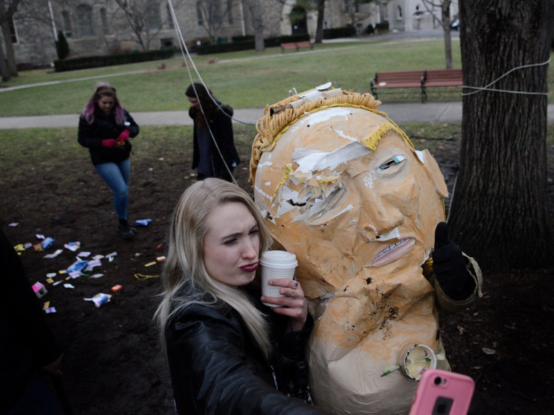 A community member poses for a selfie with the decapitated head of the Trump piñata.
