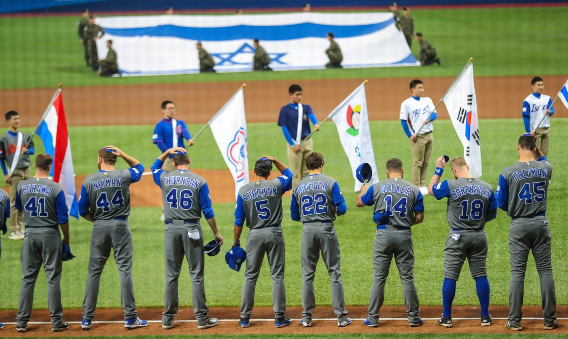 Members of Team Israel remove their caps for the national anthem during the opening ceremony of the World Baseball Classic at Gocheok Sky Dome in Seoul, South Korea, March 6, 2017. In a miracle of miracles, Israel won its tournament debut by beating South Korea, 2-1, in a game filled with walks, strikeouts and a combined 23 men left on base.