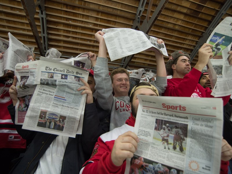 "As the starting lineup of the Harvard men's hockey team (not shown) is read, raucous Cornell fans shake copies of The Cornell Daily Sun while chanting ""Boring! Boring!"" before throwing the papers over the boards at the team. The Cornell men's hockey team would go on to beat Harvard 3-2 in that contest, the Red's first victory against Harvard since 2015. (Cameron Pollack / Sun Photography Editor)"