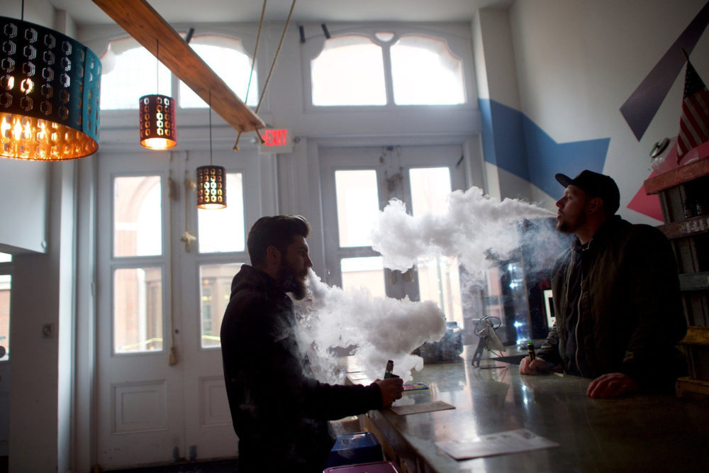 Two men vape in a store in Philadelphia. Research is inconclusive on the health effects of e-cigarettes.­