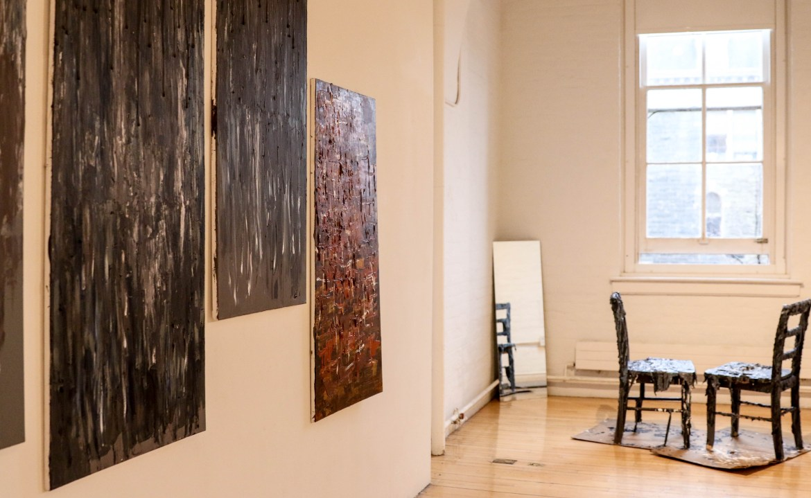 """Ariella Lindenfeld '18 arranged her exhibit """"Never Forget,"""" to capture emotions she had in reaction to events of the Holocaust. Above is her painting series """"Scrapes and Scratches"""" and sculpture """"Vanishing."""" Her exhibit also included newspaper clippings from the Holocaust, some of which were stolen on March 26."""