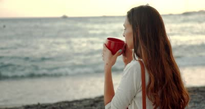 stock-footage-beautiful-young-woman-drinking-coffee-beach-sea-shore-view-boats-pier-relaxed-relaxing-vacation