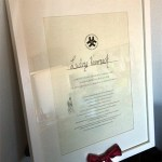 L:s diplom. Längst ner rosetten av det röda band som satt runt diplomet när han fick det vid examensceremonin.