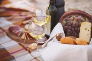 Autumn picnic by the sea with wine, grapes, bread,  jam and cheese