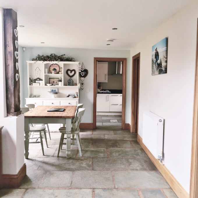 Dining area in a barn with stone floor and Farrow and Ball Pale Powder Walls