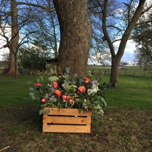 A wooden crate with roses, eucalyptus, thistles and tulips. Perfect for spring