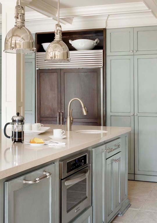 Kitchen with aqua cabinets, stainless appliances, pendant lights a small sink and a fridge with wooden doors