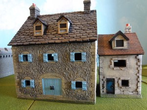 The Miniature Building Authority Stone Farm House and Stucco Town House with Dormer together outdoors.