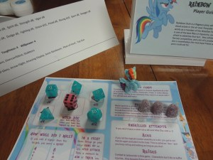 Blue dice are arranged on Savage Worlds info card with Rainbow Dash action figure