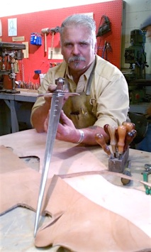David Baker admires long sword that he forged in workshop