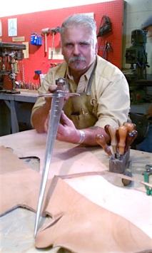 David Baker admires long sword that he forged in workshop