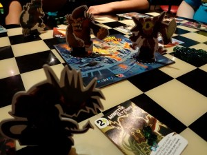Kaiju monsters from Richard Garfield's King of Tokyo game battling over its game board, giant ape versus robot with mecha-dragon in foreground