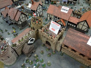 Miniature 28mm town with barracks and castle walls at Gen Con from Miniature Building Authority